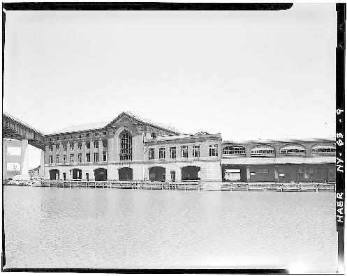 View of DL&W complex from across Buffalo River. Two passenger buildings are at center, with train shed extending toward right. Skyway shows at top left, with Naval Park construction below.