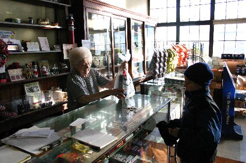 In a scene repeated thousands of time over the decades, a young neighborhood customer counts out his change to purchase Pepsi. A candy bar bonus from the owner is part of the attraction of corner delicatessen.